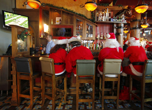Participants in SantaCon Boston 2010, a gathering of people dressed as Santa going from bar to bar, drink at the Asgard Pub in Cambridge